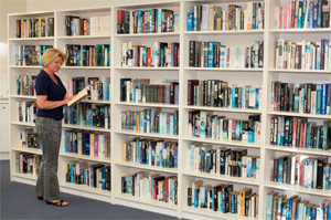A resident selecting a book from the extensive free library.
